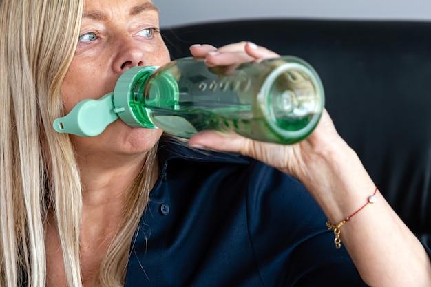 Femme blonde eau potable à partir d'une bouteille en plastique, gros plan, concept de mode de vie sain