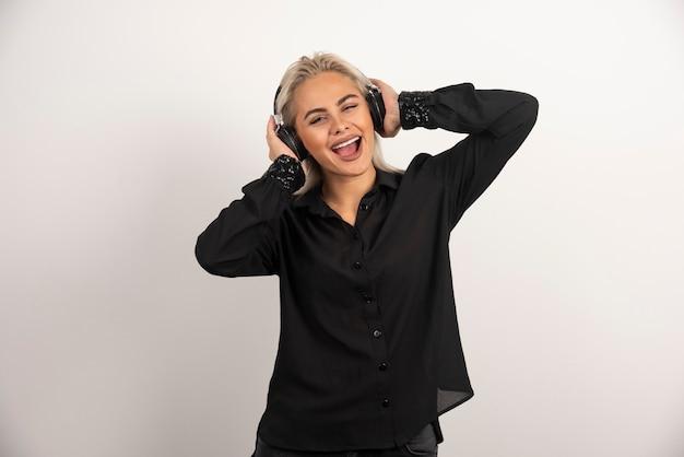 Femme blonde écoute la chanson avec des écouteurs sur fond blanc. photo de haute qualité