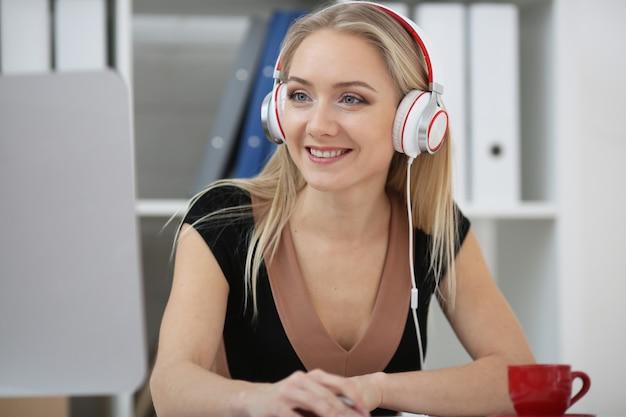 Une femme blonde écoute de la musique, regarde des films en ligne et apprend
