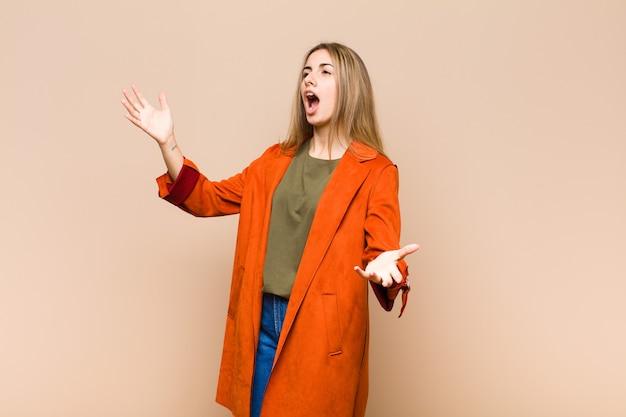 Femme blonde effectuant de l'opéra ou chantant lors d'un concert ou d'un spectacle, se sentant romantique, artistique et passionné
