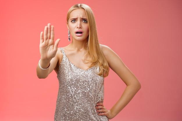Une femme blonde effrayée, mécontente et peu sûre d'elle, vêtue d'une robe argentée scintillante, étend l'arrêt de la paume suffisamment d'un geste de rejet d'interdiction dérangé énervé ennuyeux discothèque homme collant, fond rouge.