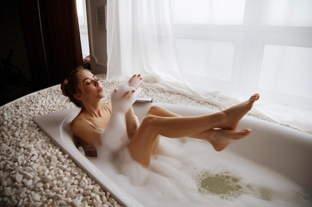 Femme blonde élancée femme prend un bain le matin avec de la mousse