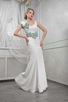 Femme blonde élégante, belle et à la mode dans une longue dre blanche