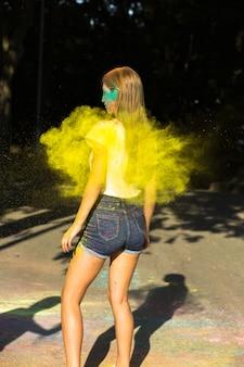 Femme blonde élégante célébrant le festival holi avec de la peinture sèche jaune