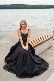 Femme blonde élégante dans une robe de nuit noire de mode près du lac, mode de vie