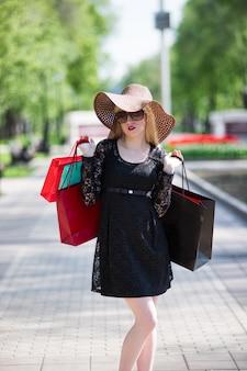 Femme blonde élégante en lunettes de soleil robe noire et chapeau avec des sacs à provisions marchant dans la ville