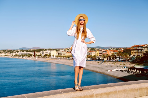 Femme blonde élégante posant devant une vue imprenable sur la plage et la ville de nice