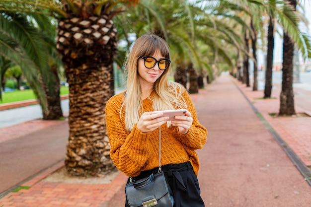 Femme blonde élégante profitant du week-end en espagne, utilisant un smartphone