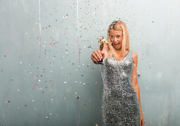 Femme blonde élégante recevant un prix, célébration avec des confettis.
