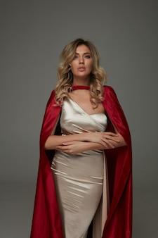 Femme blonde élégante en robe longue brillante et cape de soie rouge