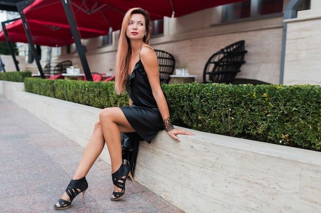 Femme blonde élégante en robe noire décontractée élégante assis près du restaurant de luxe. charmant modèle reposant en centre-ville.