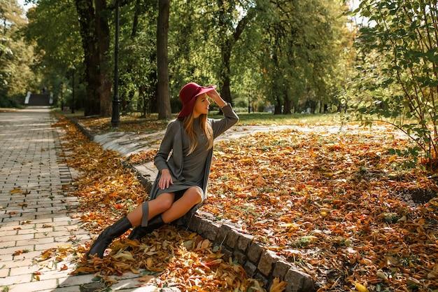 Femme blonde élégante en robe en tricot gris et chapeau rouge assis dans le parc de la ville en automne