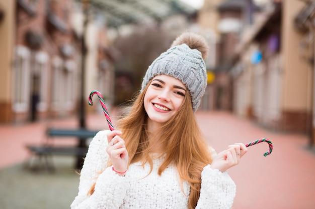 Femme blonde émotive dans le chapeau tricoté chaud posant avec des cannes de sucrerie de noël à la rue