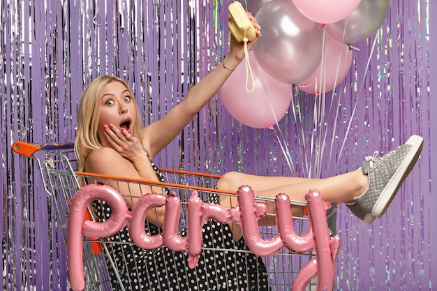 Une femme blonde émotive stupéfaite garde la bouche ouverte, tient un petit appareil photo pour faire un selfie, porte une robe à pois, des baskets, s'assoit dans un panier, étonnée par les événements récents. concept de temps de fête