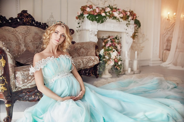 Femme blonde enceinte de luxe dans une robe de mariée.