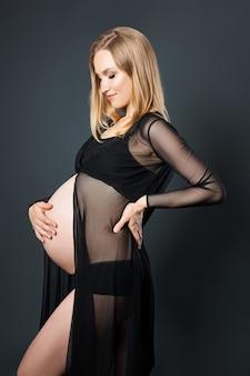 Femme blonde enceinte en sous-vêtements noirs, le neuvième mois de grossesse. maternité