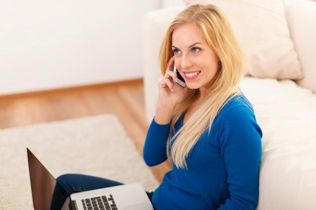 Femme blonde avec équipement électronique à la maison