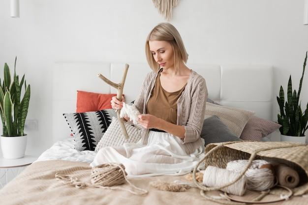 La femme blonde est assise à la maison sur le lit et tricote du macramé. femme caucasienne.