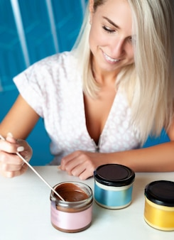 Une femme blonde est assise à une table avec de la pâte végétalienne dans des bocaux