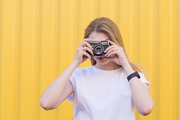 Une femme blonde est debout sur un mur jaune et fait une photo sur un vieil appareil photo argentique.