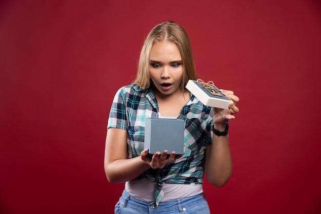 Une femme blonde est surprise en ouvrant un coffret cadeau.