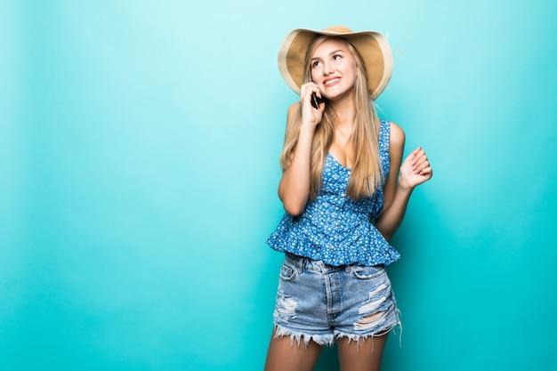 Femme blonde d'été au chapeau de paille appelant un téléphone mobile isolé sur fond blanc