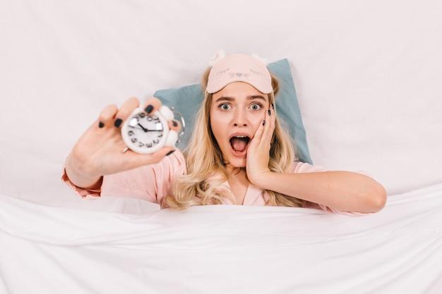 Femme blonde étonnée posant avec horloge