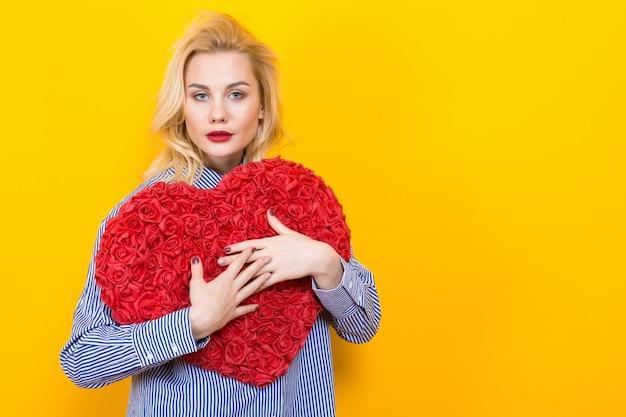 Femme blonde étreignant gros coeur de fleur rouge