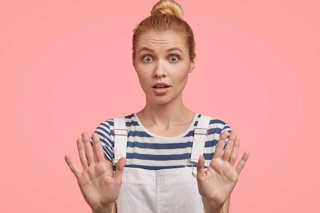 Une femme blonde européenne pose avec les mains tendues, démontre un geste d'arrêt, demande à s'arrêter, a surpris l'expression effrayée, exige de ne pas la déranger, montre l'interdiction, porte une salopette à la mode