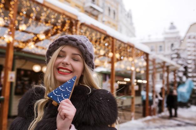 Femme blonde expressive tenant un délicieux pain d'épice contre une décoration lumineuse à la foire de noël à kiev
