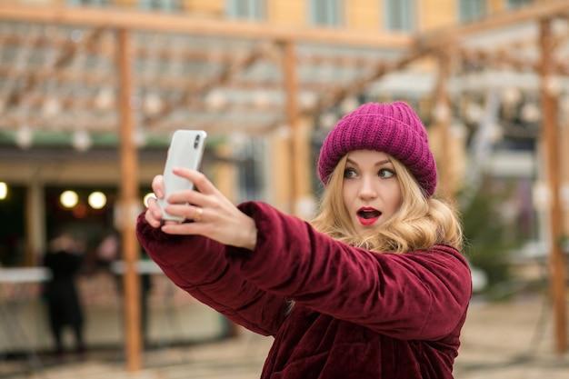 Femme blonde expressive vêtue de vêtements chauds faisant du selfie au fond de la guirlande à kiev