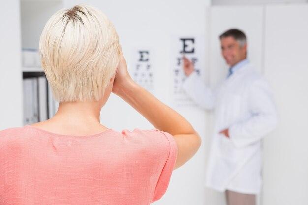 Femme blonde, faire un examen de la vue dans un cabinet médical