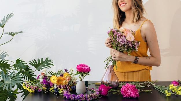 Femme blonde faisant un bouquet de fleurs