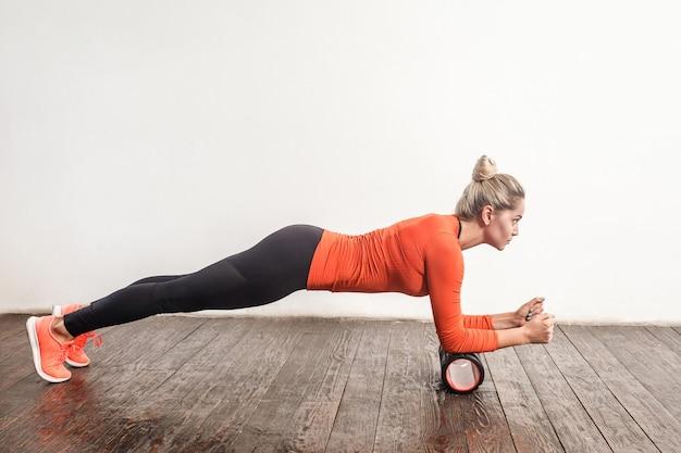 Femme blonde faisant une planche en rouleau en mousse. prise de vue en studio