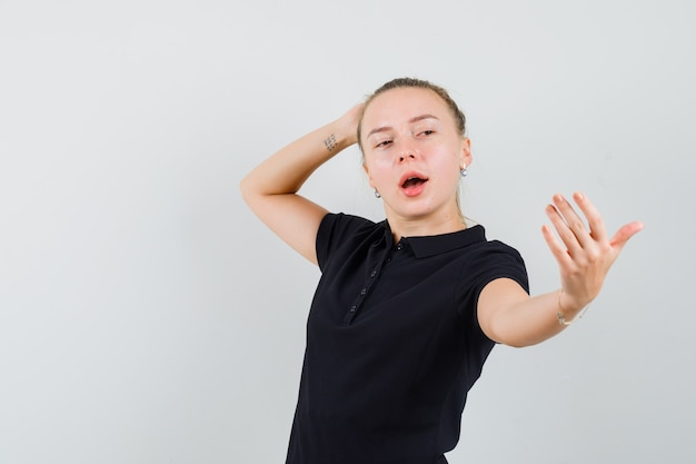 Femme blonde faisant semblant de prendre selfie en t-shirt noir