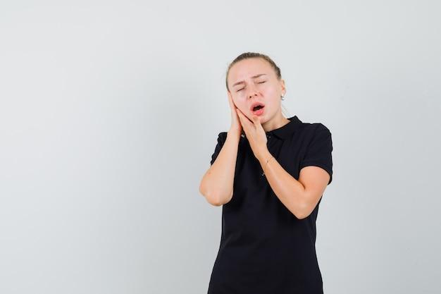 Femme blonde faisant semblant de souffrir de maux de dents en t-shirt noir et à la fatigue