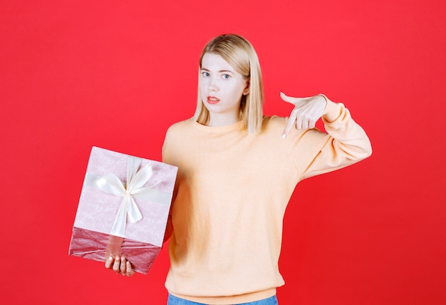 Femme blonde faisant signe de la main tout en tenant la boîte-cadeau devant le mur rouge