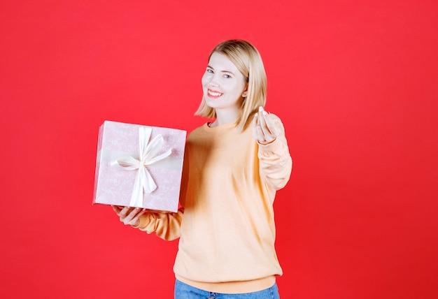 Femme blonde faisant signe de la main tout en tenant la boîte-cadeau avec sa main droite devant le mur rouge