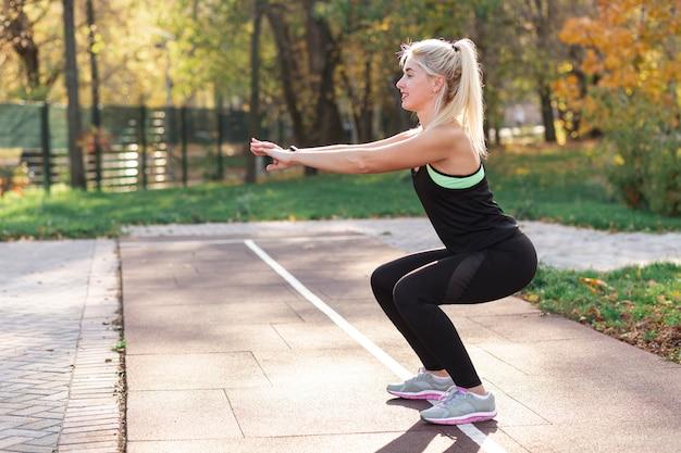 Femme blonde faisant des squats à l'extérieur