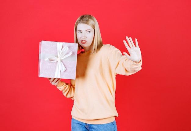 Femme blonde fait un panneau d'arrêt tout en tenant la boîte-cadeau devant le mur rouge