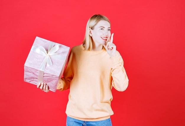 Femme blonde fait un signe de silence tout en tenant la boîte-cadeau devant le mur rouge