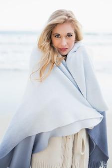 Femme blonde fashion se couvrant dans une couverture