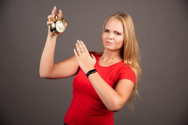 Femme blonde fatiguée avec horloge sur mur noir.