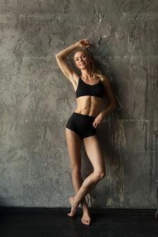 Femme blonde fitness près du mur