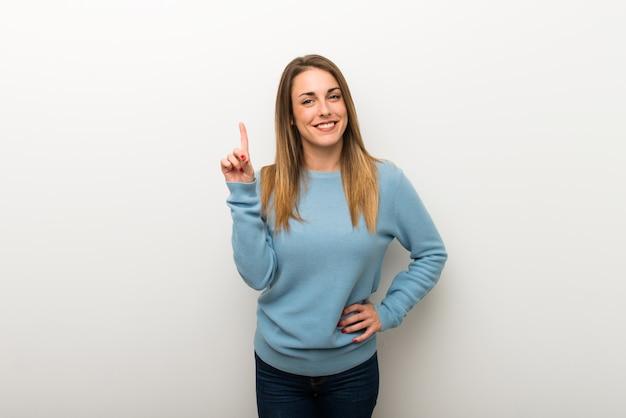 Femme blonde sur fond blanc isolé montrant et en levant un doigt en signe du meilleur