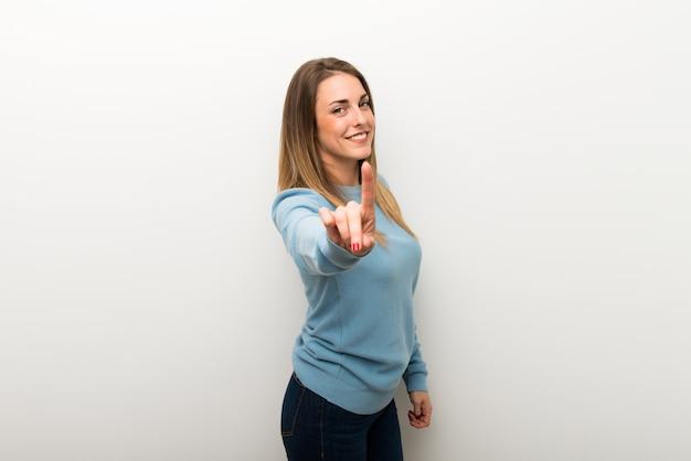 Femme blonde sur fond blanc isolé montrant et en levant un doigt