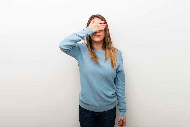 Femme blonde sur fond blanc isolé qui couvre les yeux par des mains. je ne veux pas voir quelque chose