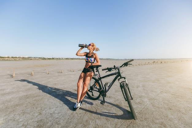 La femme blonde forte dans un costume multicolore et des lunettes de soleil se tient près d'un vélo, boit de l'eau d'une bouteille dans une zone désertique. notion de remise en forme.