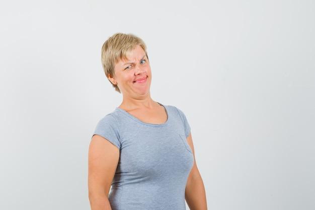 Femme blonde fronçant ses sourcils en t-shirt bleu clair et à mécontent, vue de face.