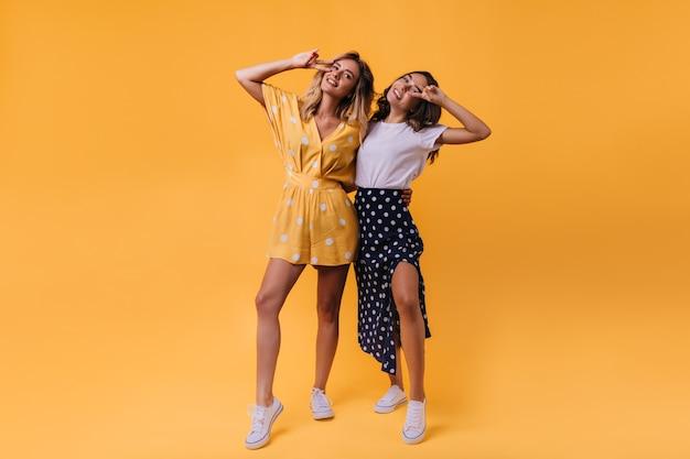 Femme blonde galbée dansant sur lumineux avec son meilleur ami. portrait intérieur de modèles féminins glamour posant avec signe de paix.